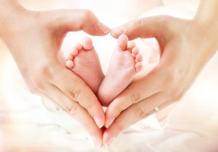nato: Piedi del bambino in mani della madre - a forma cuore
