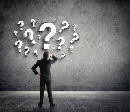 signo de interrogación: Hombre de negocios pensativo con signos de interrogación