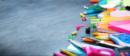 office accessories: School and office supplies on blackboard Stock Photo