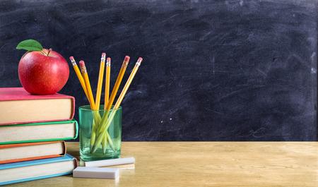 espada: manzana en los libros con los lápices y pizarra vacía - volver a la escuela