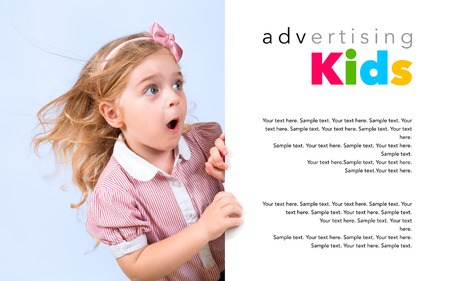 appears: little astonished girl appears behind banner Stock Photo