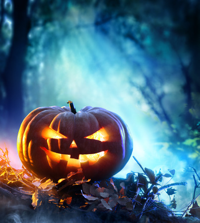 horror: Halloween Pumpkin In A Spooky Forest At Night - Scary Scene Stock Photo