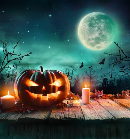 calabaza: Calabaza de Halloween en tablón de madera con velas en una noche fantasmagórica