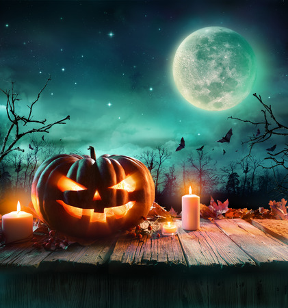 horror: Halloween Pumpkin On Wooden Plank With Candles In A Spooky Night