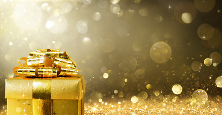 gold gift box: Christmas Present With Golden Sparkling Background