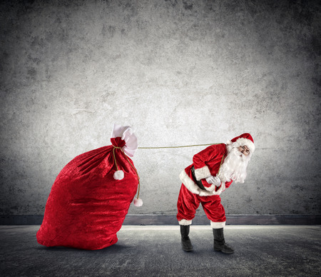 dragging: Santa Claus Dragging A Big Sack of Presents Stock Photo