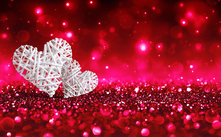 Two Wicker Hearts On Red Sparkle Glitter. Stock Photo