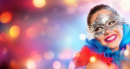 mascaras de carnaval: Mujer atractiva que sonr�e con la m�scara de Carnaval Foto de archivo