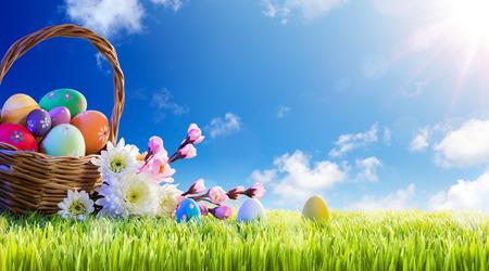 Basket of Easter Eggs With Flowers On Green Meadow Foto de archivo