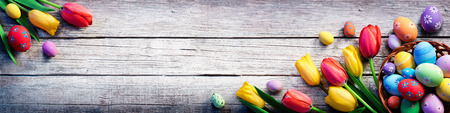 spring holiday: Tulips And Painted Eggs On Vintage Wooden Plank - Easter Background Stock Photo