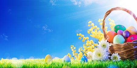Basket Of Easter Eggs peint à la main Avec Mimosa On Grass Banque d'images