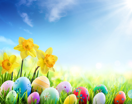 green meadow: Daffodils And Colorful Decorated Eggs On The Sunny Meadow - Easter Holiday Background Stock Photo