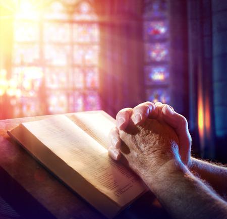 hombre orando: Las manos de un hombre que ruega con la biblia