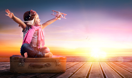 Traumreise - Kleines Mädchen auf Weinlese-Koffer bei Sonnenuntergang