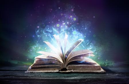 어둠 속에서 마법의 빛남과 함께 책을 매혹 스톡 콘텐츠