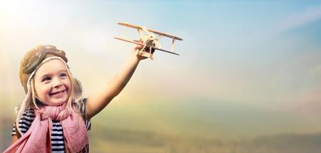 Libertà di sognare - Bambino allegro che gioca con aereo contro il cielo Archivio Fotografico - 54425396