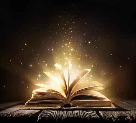 Libro viejo con las luces de magia en la tabla de la vendimia Foto de archivo - 54425402