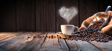 taza cafe: Taza de café con vapor tradicional en forma de corazón en la madera rústica