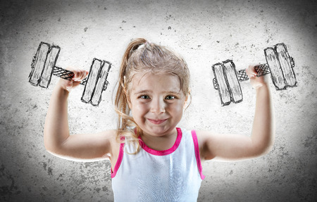 raises: Strong Child - Little Girl Raises Dumbbell Drawn On The Wall Stock Photo