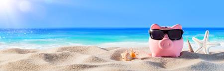 Piggy Bank mit Sonnenbrille am Strand Urlaub