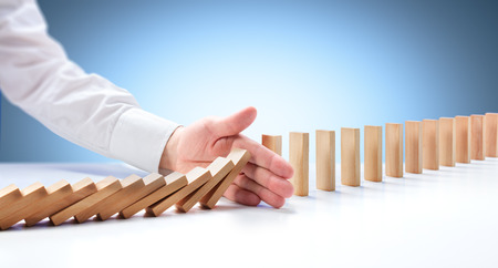 Problem Solving - Hand Stopping Domino Effect Imagens - 57658645