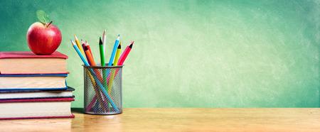 鉛筆と学校に戻る - 空の黒板書籍のスタックの上のリンゴ