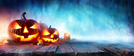 Halloween Pumpkins On Wood In A Spooky Forest At Night Stock Photo