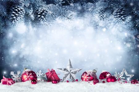 Cartolina di Natale - Bagattelle e ramo di abete sulla neve Archivio Fotografico - 63826324