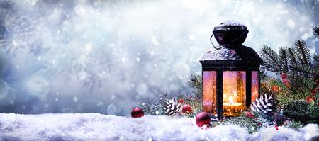 雪の上のモミの枝付きランタン
