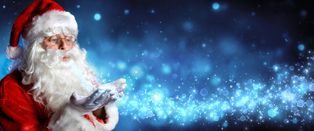 Santa Claus Blowing Magic Christmas Stars In Snowy Night Stock Photo