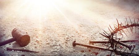 cristianismo: Pasión de Jesucristo - Martillo y clavos y corona de espinas con sangre en el suelo árido