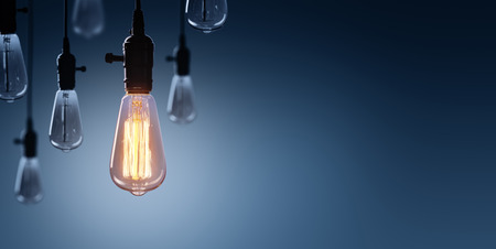 Innovation And Leadership Concept - Glowing Bulb On Bulbs Off Stock Photo