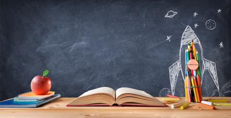 Concetto di scuola materna - rifornimenti sulla scrivania e razzo disegnato sulla lavagna
