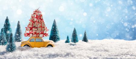 Rode auto met giften van Kerstmis In besneeuwde landschap