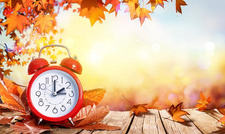 Concetto di ora legale - orologio e foglie sulla tavola di legno
