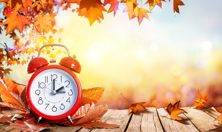 Daylight Savings Time Concept - Clock And Leaves On Wooden Table Stockfoto