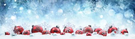 Boże Narodzenie - zdobione czerwone kulki i płatki śniegu na śniegu
