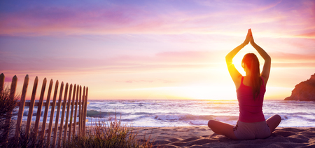 Woman Doing Yoga Fitness In The Beach At Sunset