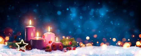 Świece adwentowe w wieńcu bożonarodzeniowym - trzy fioletowe i jeden różowy jako symbol religijny