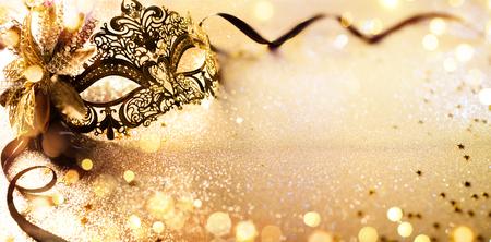 Máscara veneciana de oro en el fondo desenfocado brillante Foto de archivo - 93125952