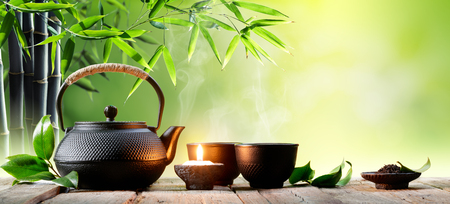 Black Iron Asian Teapot and Cups With Green Tea Leaves Stockfoto