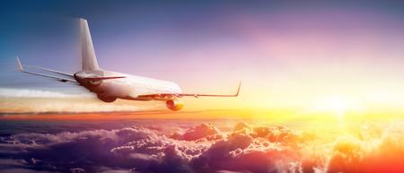Vliegtuig dat boven wolken bij zonsopgang vliegt Stockfoto