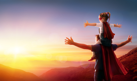 Daughter And Her Father Dressed As Heroes Watching The Sunset