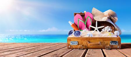 Accesorios de playa en maleta en el muelle de madera - Concepto de viaje