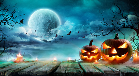 Halloween - Jack O Lanterns And Candles On Table In Misty Night Banco de Imagens