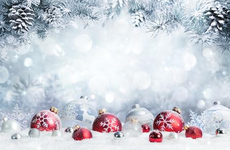 Frohe Weihnachten - Kugeln auf Schnee mit Tannenzweigen