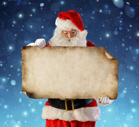 Santa Claus Reading Wish List In Snowy Night Archivio Fotografico - 112658741