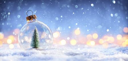 Bola de nieve con árbol de Navidad y luces sobre fondo de invierno