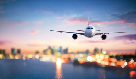 Airplane In Flight At Twilight With Blurred Cityscape Archivio Fotografico - 116640068