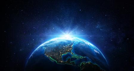 Wschód słońca w kosmosie - niebieska ziemia ze światłami miasta -